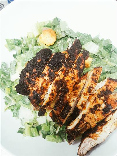 grilled chicken strips on a bed of lettuce