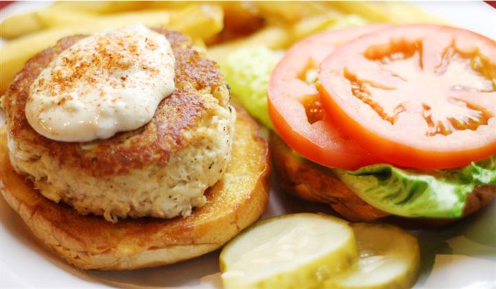crab cake on a bun topped with sauce with lettuce and tomato on the side