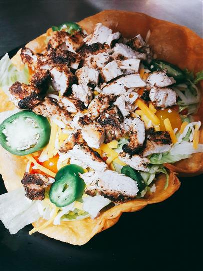 grilled chicken over lettuce with shredded cheese in a taco shell