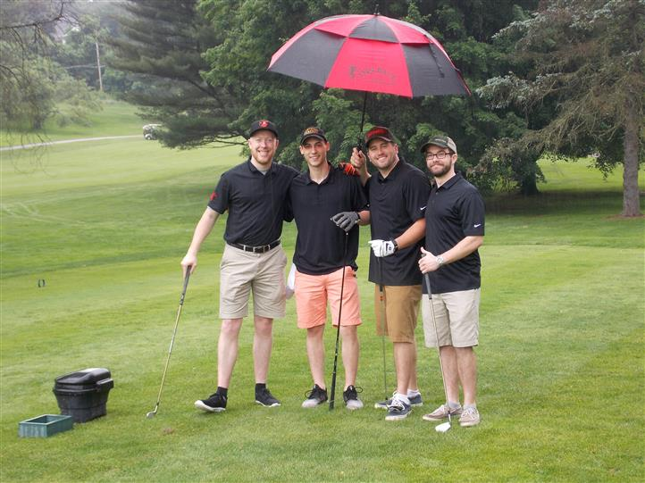 four men posing for picture under umbrella