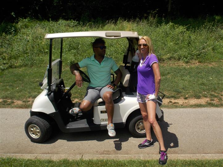 male sitting in golf cart with female posing next to it