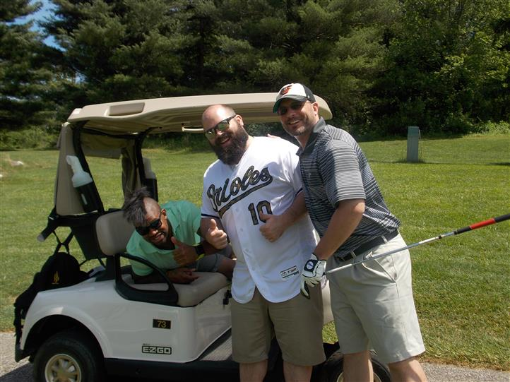 men posing for picture next to golf cart