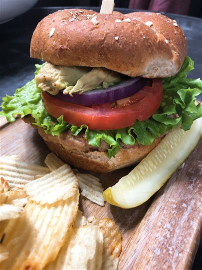 chicken sandwich on a bun with lettuce, tomato and a pickle and potato chips on the side