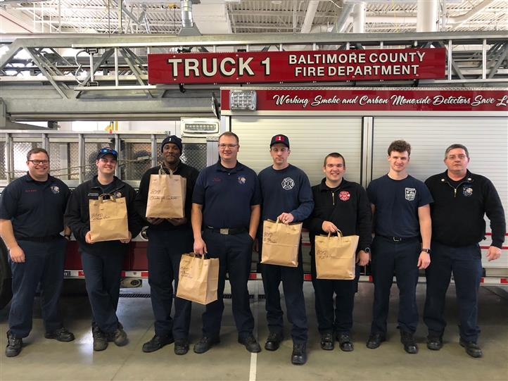 firefighters holding bags standing in front of a firetruck