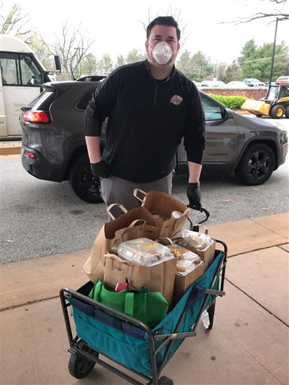 male wearing masks pushing cart full of food