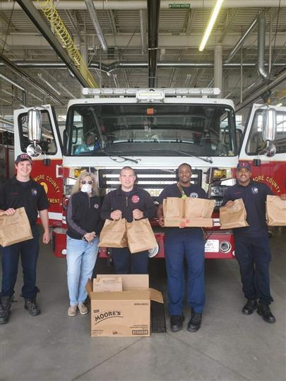 firefighters holding bags of food