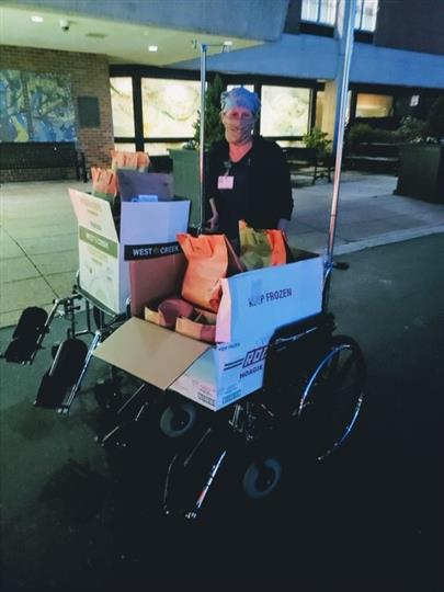 man wearing mask with cardboard boxes of food