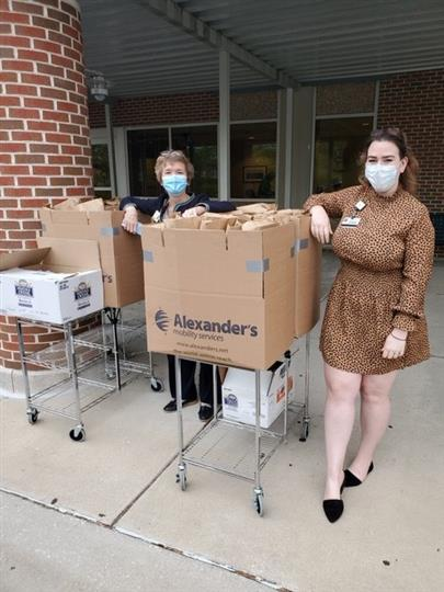 females wearing mask with cardboard boxes of food