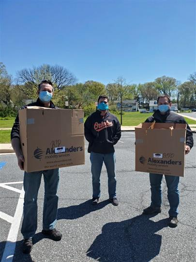 men wearing masks with cardboard boxes of food