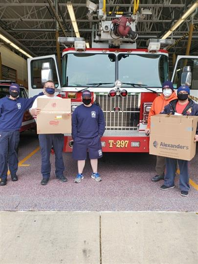 men wearing masks with cardboard boxes of food in front of firetruck
