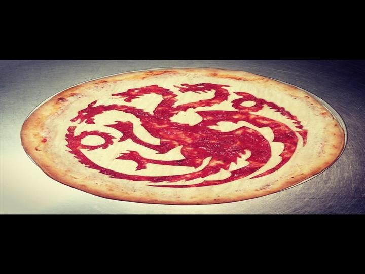 A pizza crust with dragons carved into it