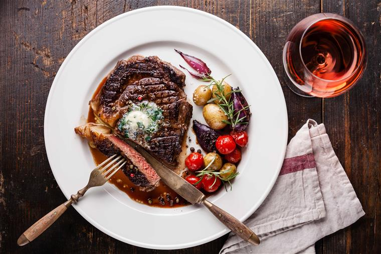steak cooked medium rare on a white plate with potatoes and a glass of red wine