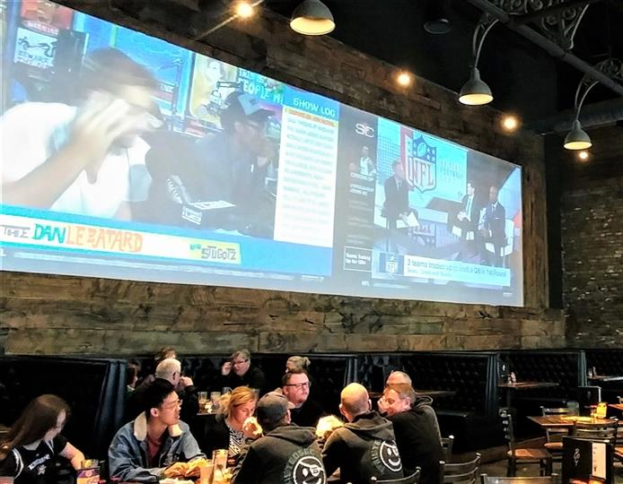 customers at tables inside brew garden with huge televisions on the wall