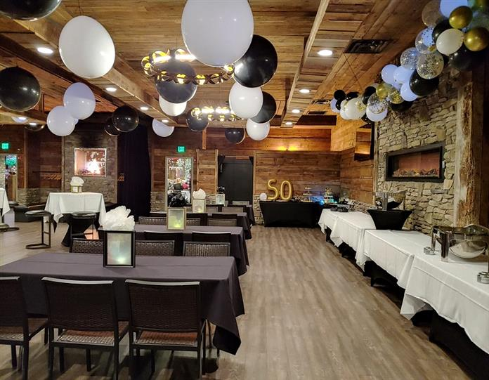 another view of party room with big balloons hanging from the ceiling and tables with cloths