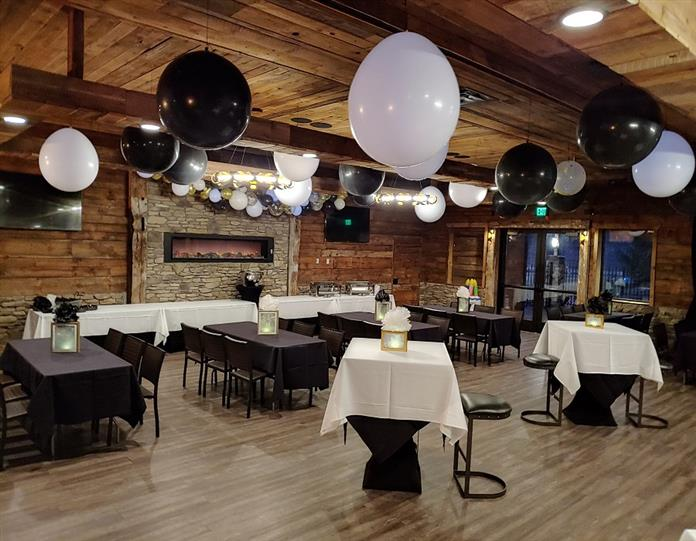 party room with big balloons hanging from the ceiling and tables with cloths