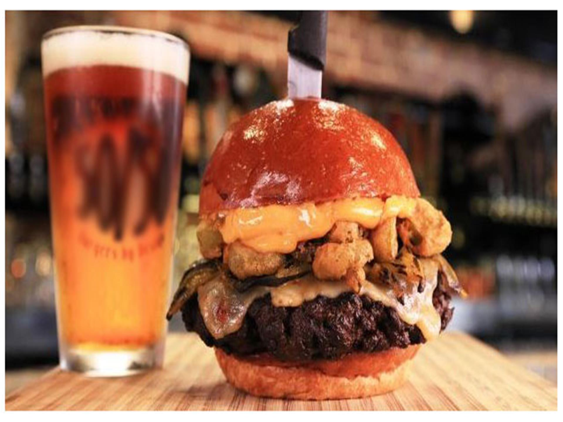 Thick burger with knife through top bun next to full beer glass.