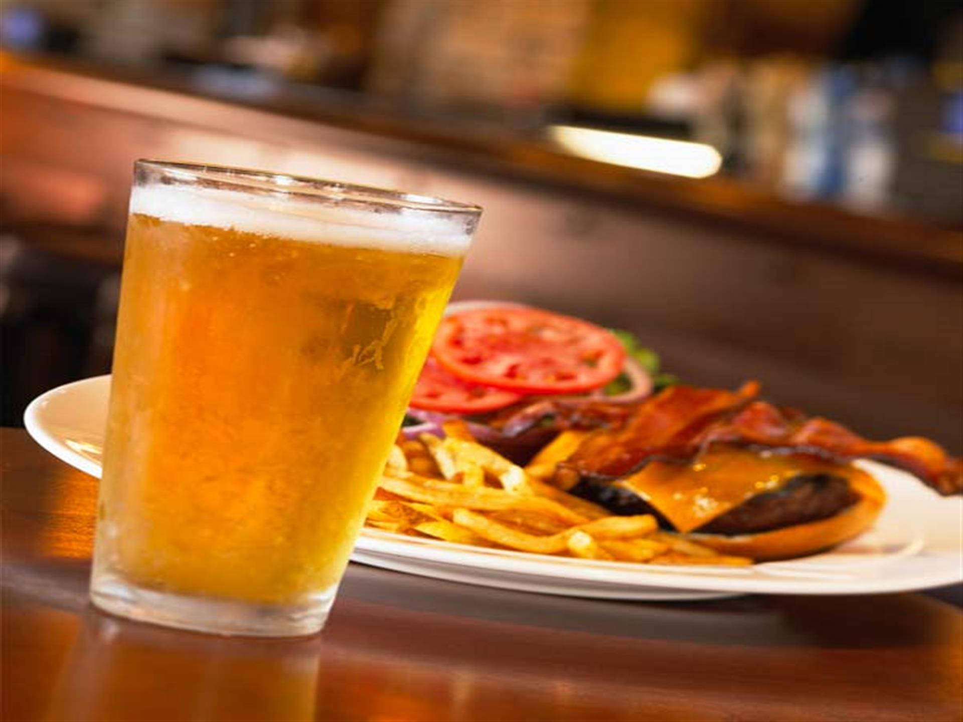 Open-faced burger with cheese, bacon, tomato, onions, lettuce and side of fries behind full beer glass