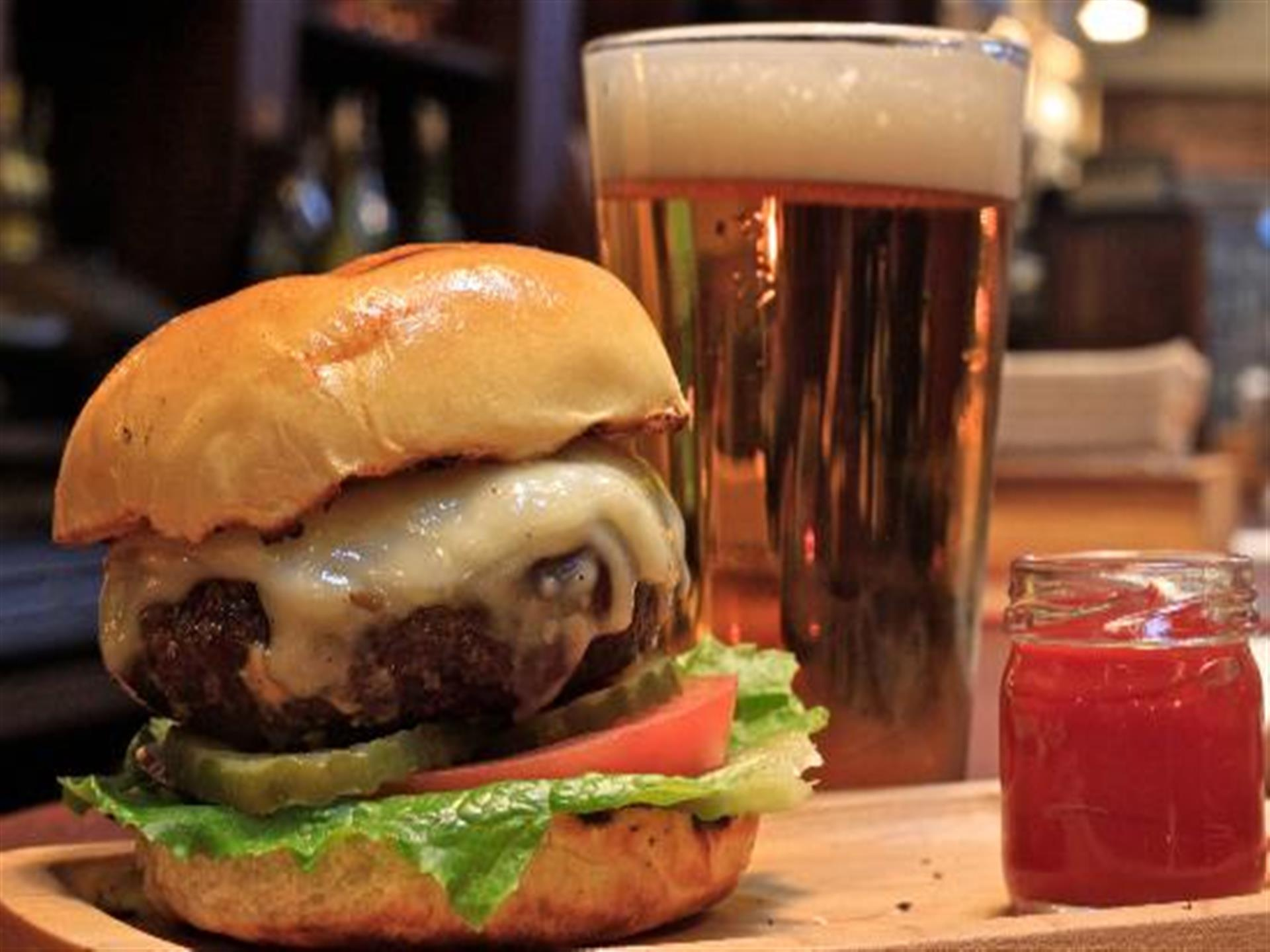 Thick burger with cheese, lettuce, pickle, tomato on bun with side of ketchup and full beer glass