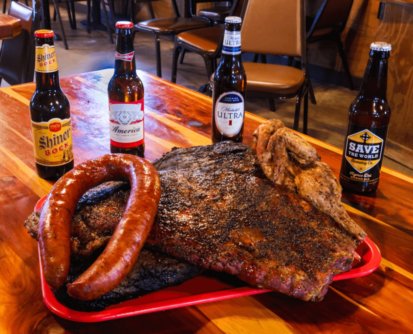 Large tray with barbequed meats and bottles of beer set on a table