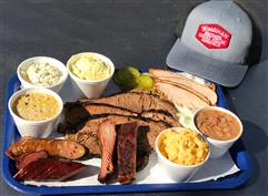 Tray with assorted meats and side dishes on on the side next to a grey cap on a table