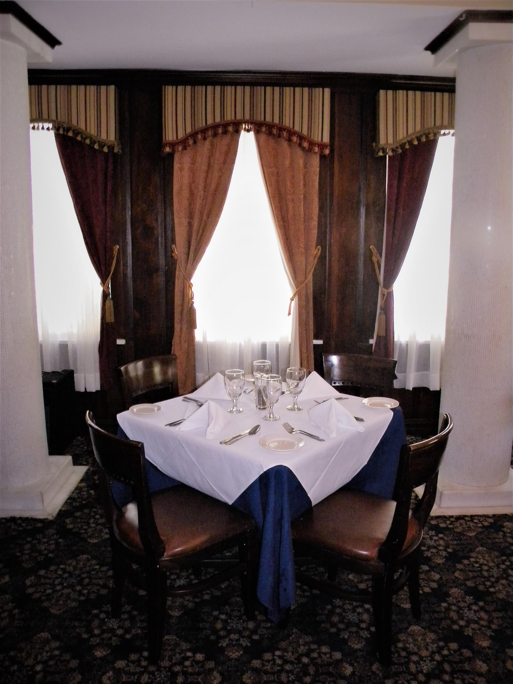 an indoor table with a white table cloth and four chairs and place settings