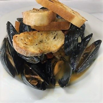 a bowl of mussels in sauce with garlic bread on top
