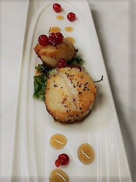 two scallops in a sauce with sesame seeds