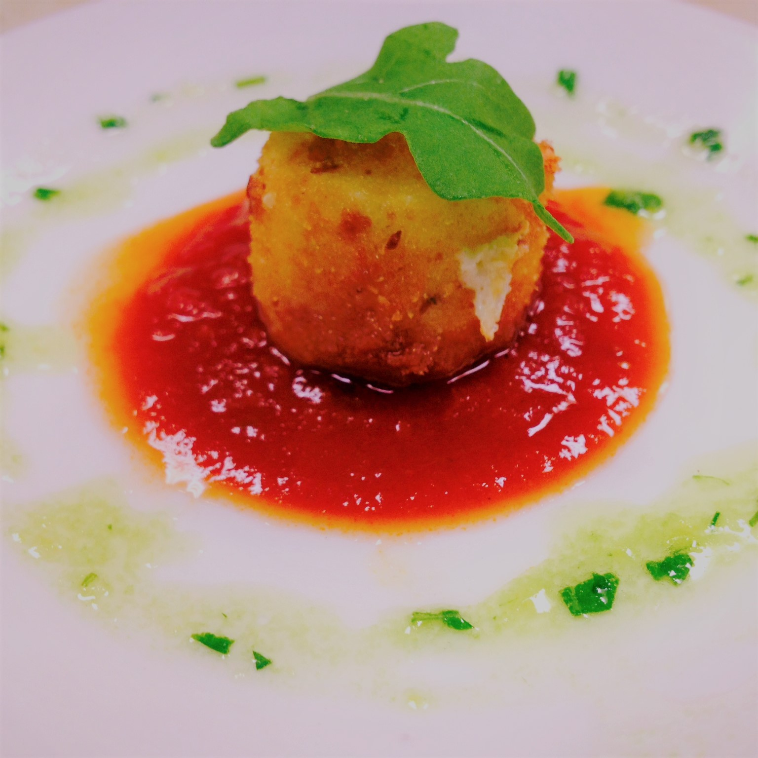 a single scallop on a plate in sauce