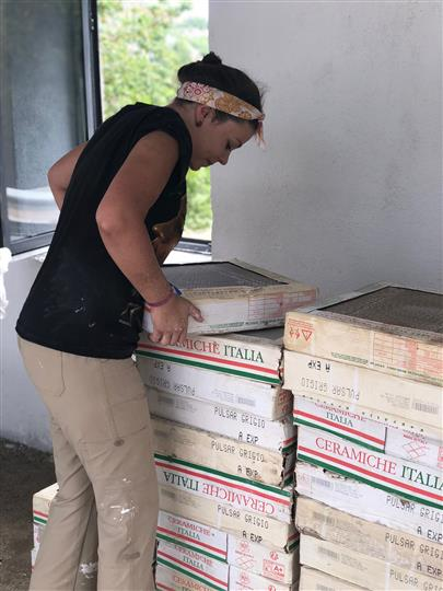 Woman with a pile of pizza boxes