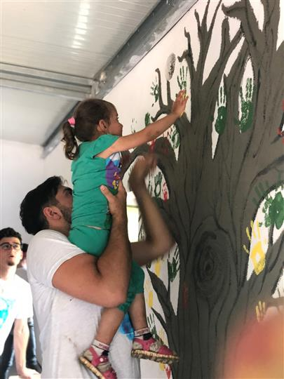 Man holding little girl to put handprint on tree