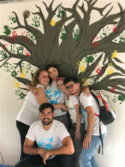 Group standing in front of painted tree with handprints for leaves