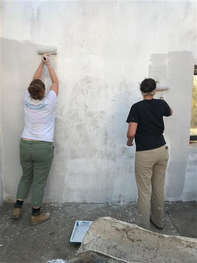 Two people painting a wall with a rollerbrush