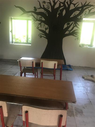 Finished painting of tree on wall with tables and chairs