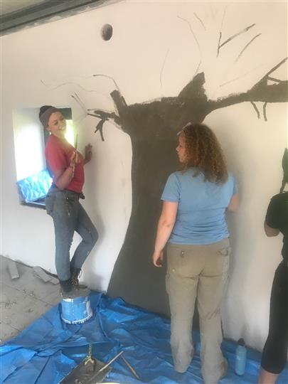 Two woman beginning to paint a tree on wall