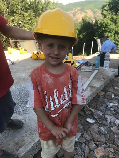 Adorable little child smiling with yellow hard hat on