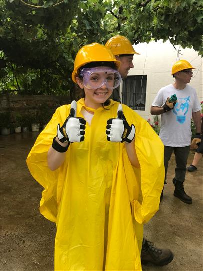 Girl with yellow rain poncho, hard hat, and clear goggles