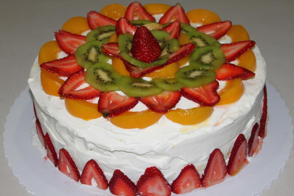 Cake with white icing topped with peaches, strawberries and kiwi slices