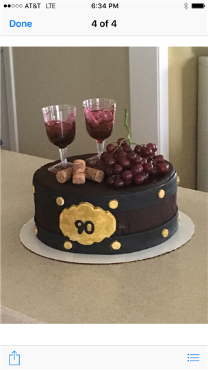 cake topped with two wine glasses and grapes and corks