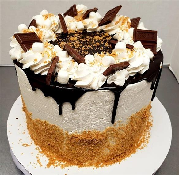 cake with hershey's bar, whipped cream, and chocolate drizzle on top