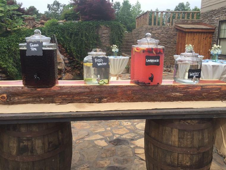 An outdoors photo of a decorated wooden board on barrels having beverages in glass pots.