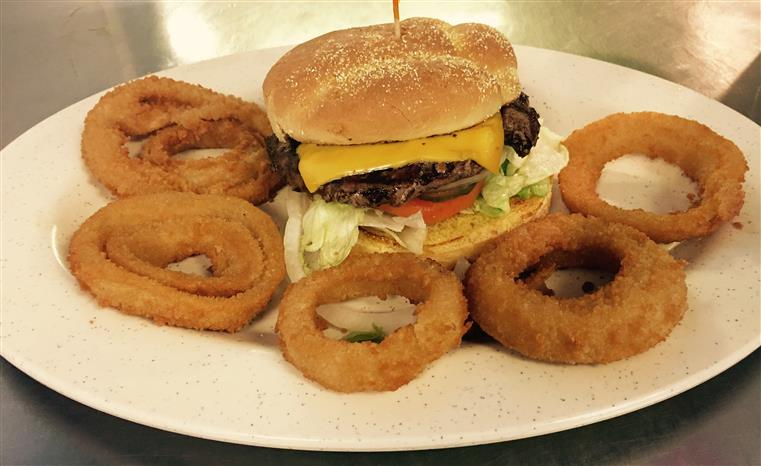 cheeseburger with lettuce and tomato with onion rings on the side.
