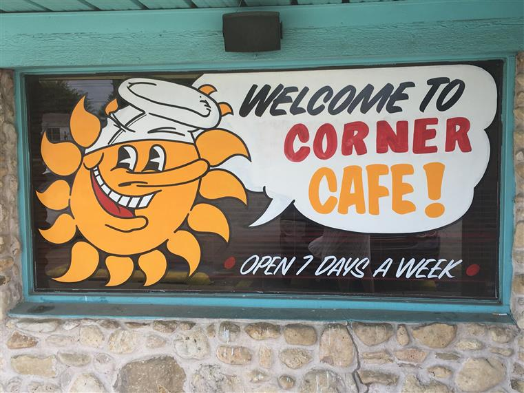 """Welcome to Corner Cafe"" painted on window with cartoon sun"