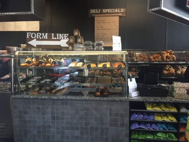"Front counter of store showing a glass with pastries behind it & a sign that says ""Form line"""