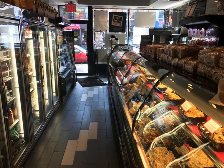 Front of store that shows food behind glass under the counter and refrigerators holding beverages