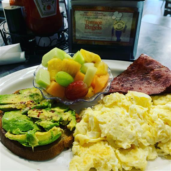 a plate with scranbled eggs, toast with avocado, a cup of fruit and canadian bacon