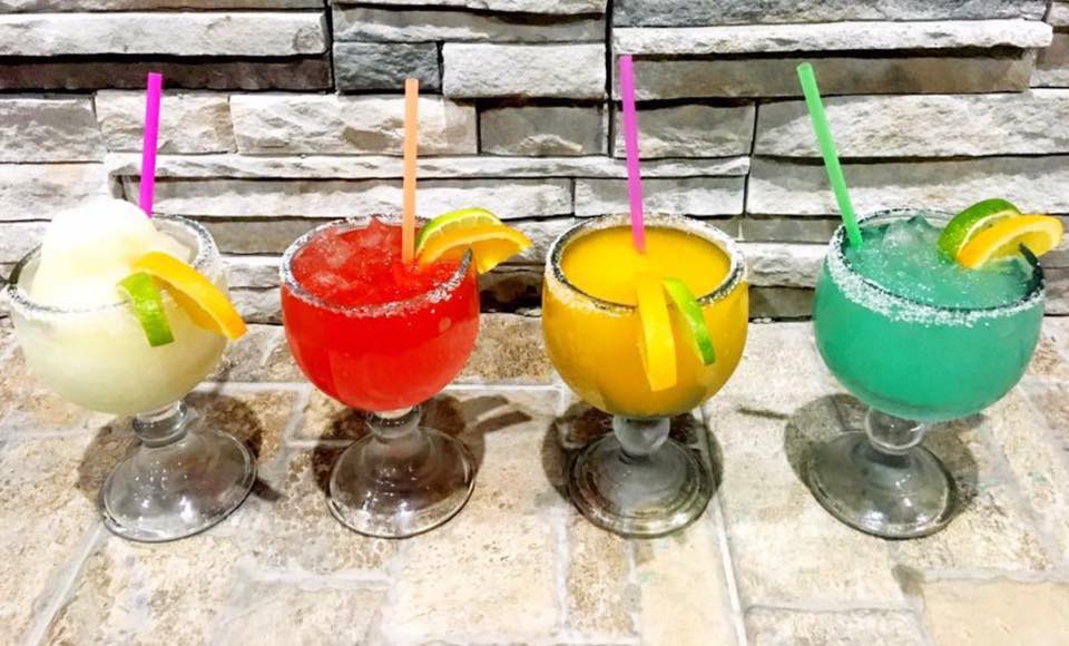 four margaritas on a brick counter