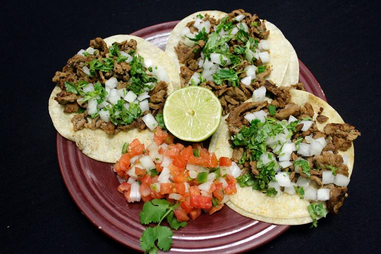 three soft shell beef tacos with pico de gallo, onion, and cilantro and a lime
