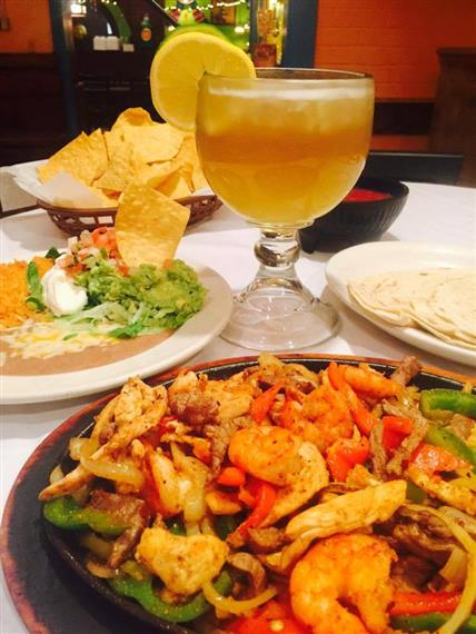 a plate of grilled vegetables fajita with shrimp and a margarita with a side dish of tortilla chips and dip