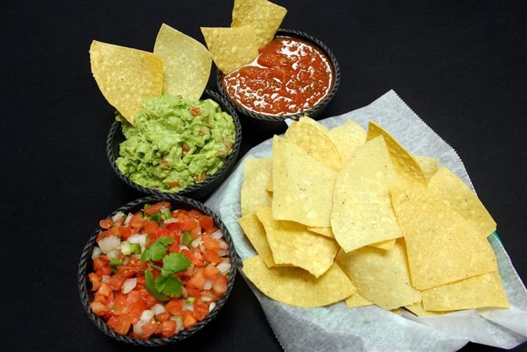 tortilla chips in a basket with a side of salsa, guacamole, and pico de gallo
