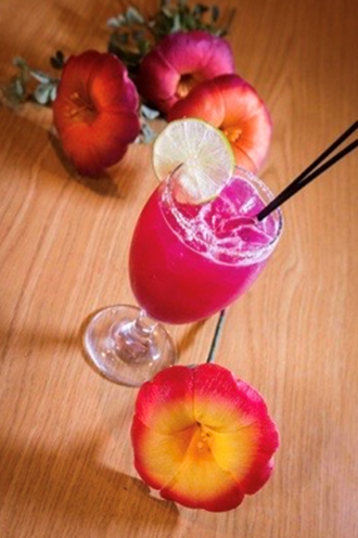 pink alcoholic drink with a lime wedge and flowers on the table